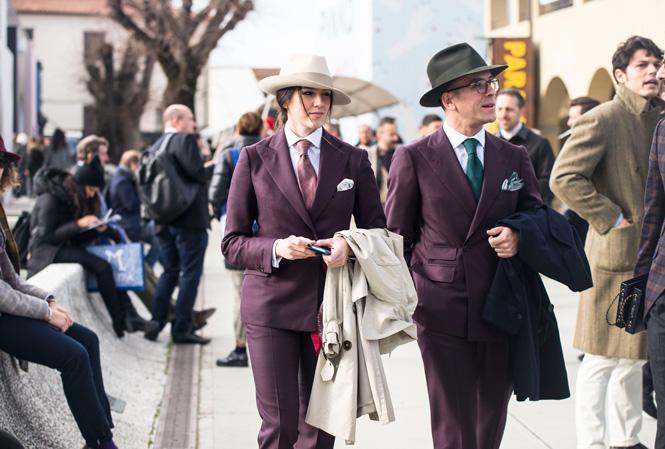 Ett par som båda går i lila kostym och hatt