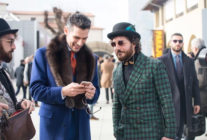 Man i rock med pälskrage visar en annan man något på sin telefon