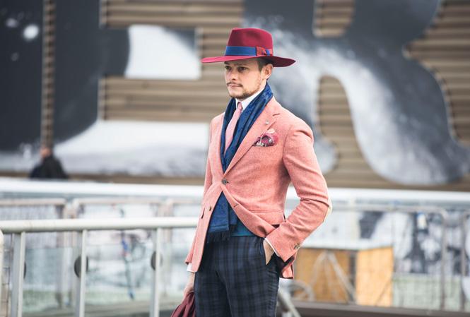 En som bär rosa kavaj och hatt