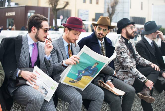 Välklädda män som sitter och röker och läser tidningen