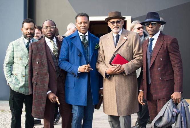 Fem välklädda män i färgglada rockar
