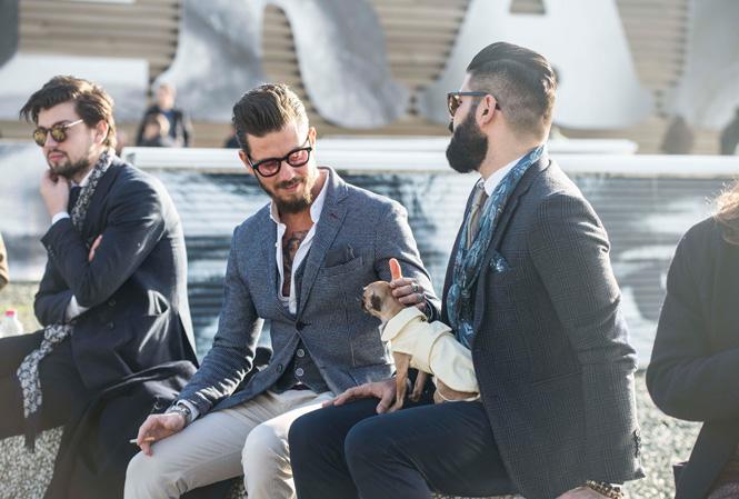 Två män som sitter och pratar och en liten hund