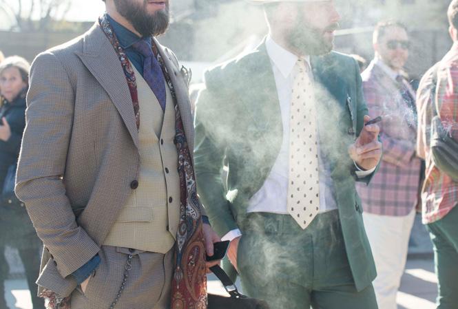 Två välklädda män som står och röker