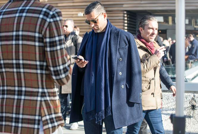 Man som står och kollar på sin telefon