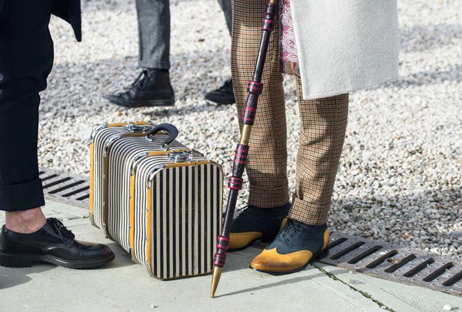 Man poserar med käpp, framför koffert